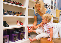 Mother with Toddler girl trying on shoes in a childrens clothing store..Model Property/Releases.20070820_MR_C.20070820_MR_B.20070820_PR_A