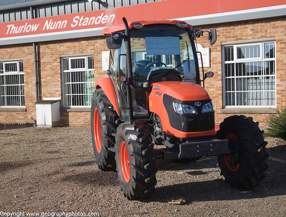 Brand new red Kubota M7040 tractor on sales forecourt, Melton, Suffolk, England