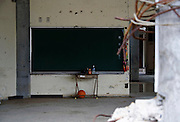 A ball and other otems lie underneath a blackboard  inside the batter remains of Okawa Elementary school in Ishinomaki, Miyagi Prefecture, Japan on 24 Feb. 2012. . .Photographer: Robert Gilhooly