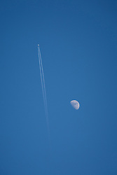 © Licensed to London News Pictures . 17/03/2016 . Salford , UK . An aeroplane crosses a clear blue sky , juxtaposed with the moon , during a warm spring afternoon in the UK , as viewed from Salford . Photo credit : Joel Goodman/LNP