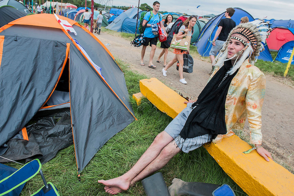 Contemplating his first Glastonbury, with a clash of ethnic themes, from his camp above the Pyramid Stage. The 2014 Glastonbury Festival, Worthy Farm, Glastonbury. 26 June 2013.  Guy Bell, 07771 786236, guy@gbphotos.com