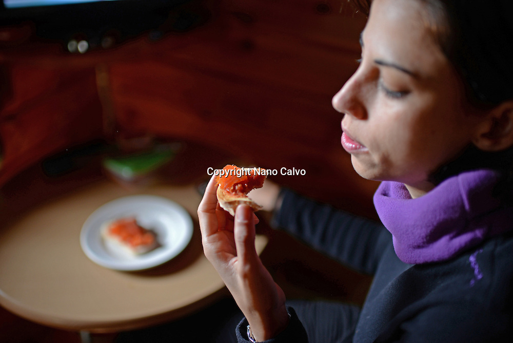 Young woman eats toast with salmon in wood cottage