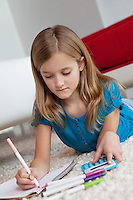 Blond girl doing homework while lying down on rug