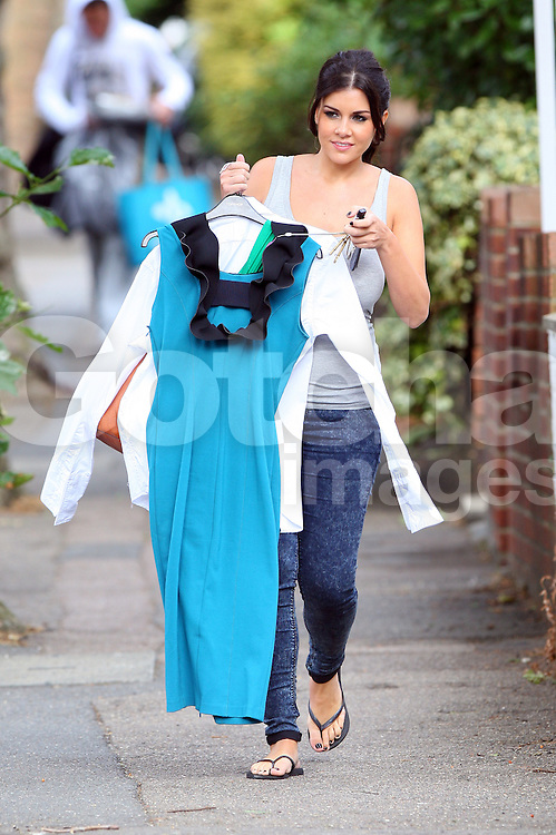 Pregnant model Imogen Thomas wearing a grey vest top and jeans picks up some dry cleaning with her boyfriend Adam Horsley in north London, UK. 14/09/2012<br />