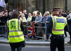 © Licensed to London News Pictures . 27/09/2018. London, UK. A woman wears a high visability jacket with a picture of former EDL leader Tommy Robinson on before he arrives at the Old Bailey for a retrial for Contempt of Court following his actions outside Leeds Crown Court in May 2018 . Robinson was already serving a suspended sentence for the same offence when convicted in May and served time in jail as a consequence , but the newer conviction was quashed by the Court of Appeal and a retrial ordered . Photo credit: Peter Macdiarmid/LNP