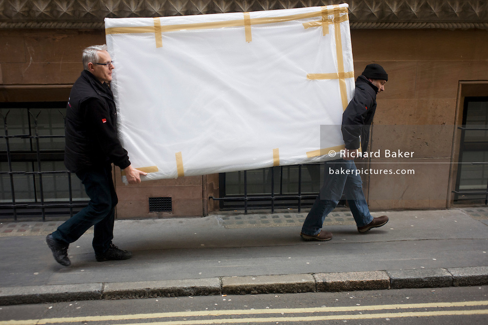 Destined for nearby offices, two workmen deliver a heavy piece of corporate art taped up and covered in a narrow side street in the City of London, the capital's financial district. Each manhandling a corner and sharing the weight of this awkward company asset. Taped up for protection and handled carefully, the men make their way along a narrow medieval street called Tokenhouse Yard. This street dates from Charles I and was where farthing tokens were coined. The City of London is the capital's historic centre first occupied by the Romans then expanded during following centuries until today, it has a resident population of under 10,000 but a daily working population of 311,000.
