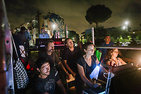 """ROME, ITALY - 27 JUNE 2017:  Director Fabio Cherstich (center), technicians and assistant watch the final moments of the  """"Don Giovanni OperaCamion"""", an open-air opera performed on a truck in San Basilio, a suburb in Rome, Italy, on June 27th 2017.<br /> <br /> Director Fabio Cherstich's idae of an """"opera truck"""" was conceived as a way of bringing the musical theatre to a new, mixed, non elitist public, and have it perceived as a moment of cultural sharing, intelligent entertainment and no longer as an inaccessible and costly event. The truck becomes a stage that goes from square to square with its orchestra and its company of singers in Rome. <br /> <br /> """"Don Giovanni Opera Camion"""", after """"Don Giovanni"""" by Wolfgang Amadeus Mozart is a new production by the Teatro dell'Opera di Roma, conceived and directed by Fabio Cherstich. Set, videos and costumes by Gianluigi Toccafondo. The Youth Orchestra of the Teatro dell'Opera di Roma is conducted by Carlo Donadio."""
