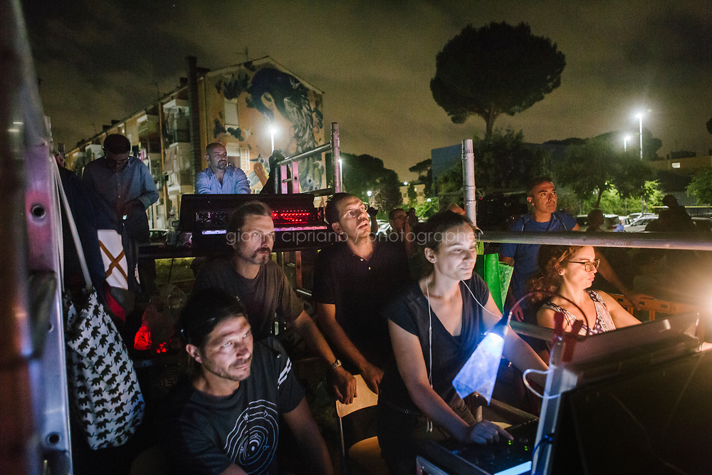 ROME, ITALY - 27 JUNE 2017:  Director Fabio Cherstich (center), technicians and assistant watch the final moments of the  &quot;Don Giovanni OperaCamion&quot;, an open-air opera performed on a truck in San Basilio, a suburb in Rome, Italy, on June 27th 2017.<br /> <br /> Director Fabio Cherstich&rsquo;s idae of an &ldquo;opera truck&rdquo; was conceived as a way of bringing the musical theatre to a new, mixed, non elitist public, and have it perceived as a moment of cultural sharing, intelligent entertainment and no longer as an inaccessible and costly event. The truck becomes a stage that goes from square to square with its orchestra and its company of singers in Rome. <br /> <br /> &ldquo;Don Giovanni Opera Camion&rdquo;, after &ldquo;Don Giovanni&rdquo; by Wolfgang Amadeus Mozart is a new production by the Teatro dell&rsquo;Opera di Roma, conceived and directed by Fabio Cherstich. Set, videos and costumes by Gianluigi Toccafondo. The Youth Orchestra of the Teatro dell&rsquo;Opera di Roma is conducted by Carlo Donadio.