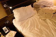 Unmade double bed in luxury room in Sofitel at Heathrow's terminal 5.