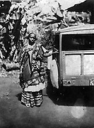 At a time, the Makina section of Kibera was filled with spacious compounds and homesteads.  A woman takes a photo near a banana plantation with the family car.  (1948)