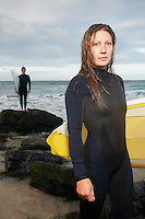Female surfer carrying surfboard standing on beach another surfer standing in background portrait