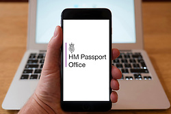 Using iPhone smartphone to display logo of UK Home Office Border and Immigration Service.