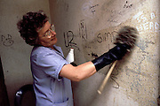 Council cleansing dept cleaner removing graffiti from a toilet wall