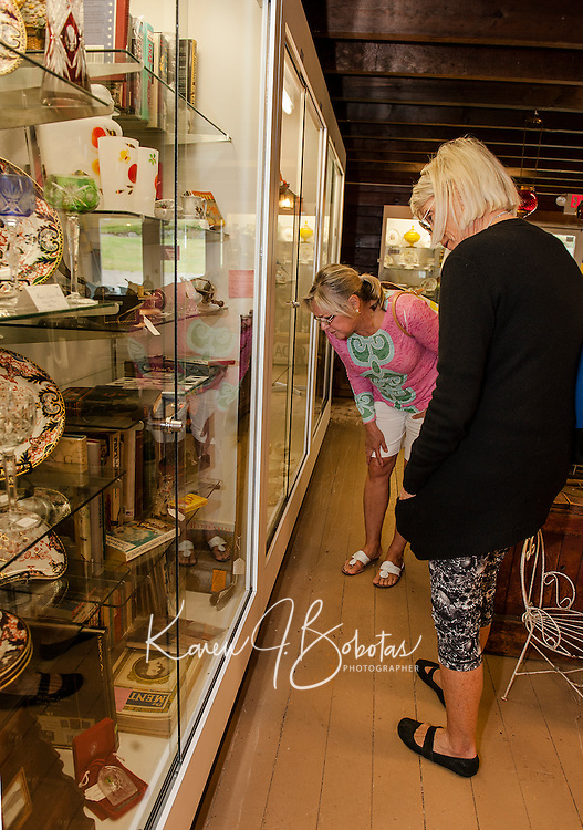 Carol Hovey and Suzy Beech browse through Paws Antiques in Meredith on Thursday afternoon.  (Karen Bobotas/for the Laconia Daily Sun)