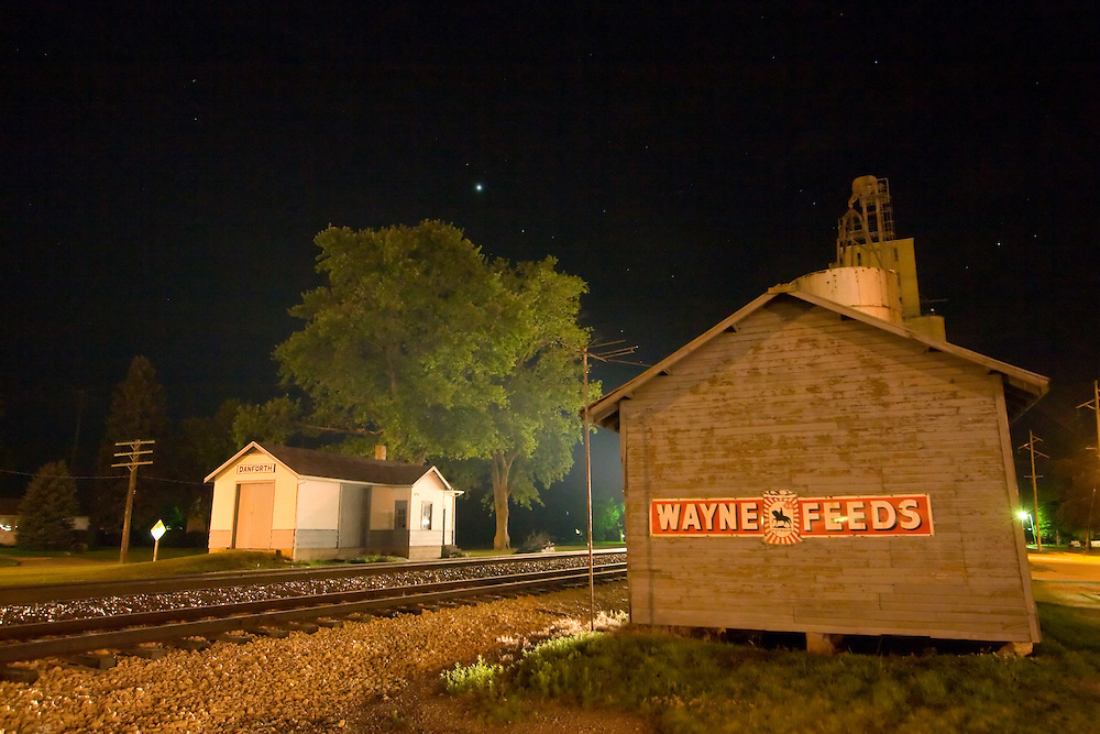 A fast approaching train lights up the restored town depot and trackside trees of the small east central Illinois town of Danforth, complete with an old style grain elevator complex.