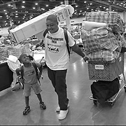 "New Orleans Hurricane Katrina evacuees Eddie Nelson, and his son, ""Little"" Eddie III, 5, move out of the Reliant Center in Houston, Texas on September 10, 2005, 13 days after the storm devastated the Gulf Coast. A Houstonian and her family and friends helped place sixteen members their extended family in three FEMA-subsidized  apartments in the Sharpstown apartment complex in southwest Houston, Texas which they fully equipped with furniture, clothes and food.  The family was living in the shelter after being relocated from the Superdome following their voluntary evacuation before the storm hit. A documentary project, part of which was published by The New York Times, about Eddie and Denise Nelson and their family, a New Orleans African-American family who were displaced by Hurricane Katrina and became part of the diaspora living in Texas. A documentary project, part of which was published by The New York Times, about Eddie and Denise Nelson and their family, a New Orleans African-American family who were displaced by Hurricane Katrina and became part of the diaspora living in Texas."