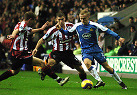 Photo: Paul Greenwood.<br />Wigan Athletic v Sheffield United. The Barclays Premiership. 16/12/2006. Wigan's David Cotterill, right, gets into a tight spot as Chris Armstrong, left and  Nick Montgomery, centre, close in.