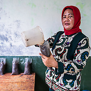 """CAPTION: It's not only the students who've benefited from ACCCRN's education project. Dwi's teacher, Ms Sunarsih, talks of how her habits have changed since she's learned about the significance of climate change. ''Before this programme, we would just sweep up the leaves that fell from the trees; now, we use them for composting"""", she says. """"I've started planting trees and plants, and these days I'm even concerned about people cutting down trees from the hills, owing to the flooding it causes"""". LOCATION: SMP N 7 School, Bandar Lampung, Indonesia. INDIVIDUAL(S) PHOTOGRAPHED: Ms Sunarsih."""