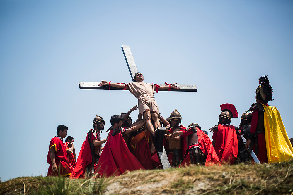 A devout Catholic is raised up on a cross during the Holy Week festival in Pampanga, the Philippines.