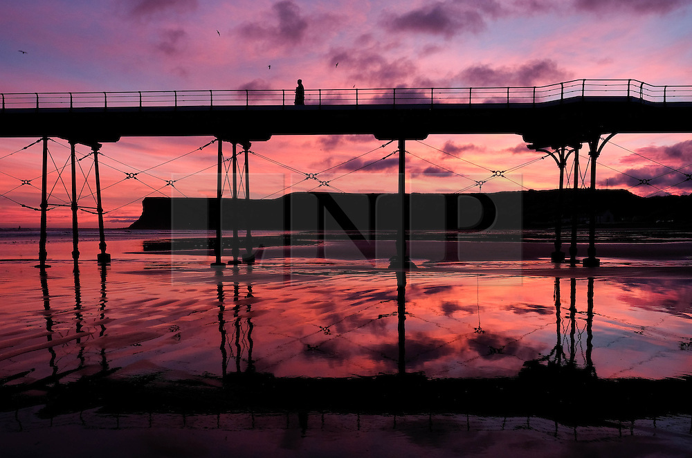 © Licensed to London News Pictures. <br /> 25/12/2016. <br /> Saltburn-by-the-Sea, UK.  <br /> <br /> A woman walks along the pier as the first light of dawn illuminates the sky on Christmas morning in Saltburn by the Sea.<br /> <br /> <br /> Photo credit: Ian Forsyth/LNP