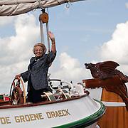 Nederland,Offingawier,11-08-2010 Koningin Beatrix aan het roer van het koninklijke jacht De Groene Draeck varend op het Snekermeer. De koningin bezoekt het zeil evenement De Sneekweek tijdens Hardzeildag. Het evenement wordt dit jaar voor de 75e keer gehouden. Dutch Queen Beatrix at the rudder of her traditional yacht The Groene Draeck during a sailing event called the Sneekweek. FOTO: Gerard Til