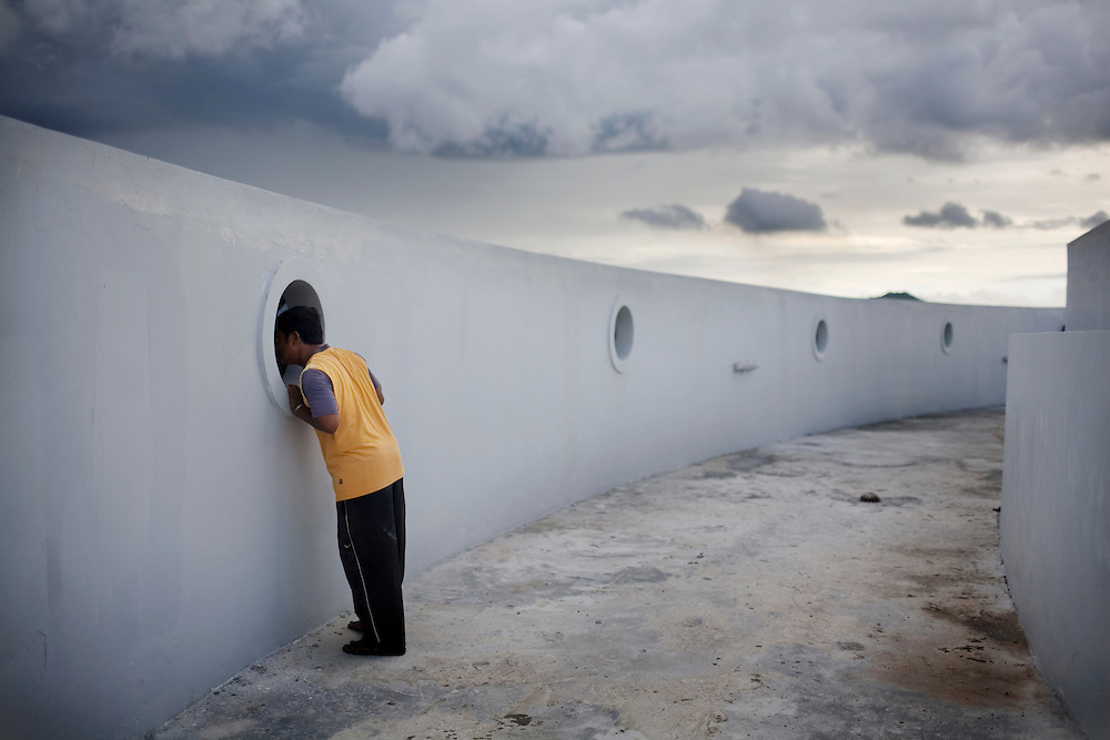 A gatekeeper, of the Tsunami Museum, takes a peek out of portal window to the view below from the roof of the museum, which is now closed due to lack of funding, in Banda Aceh, Sunday, Nov. 8, 2009. Beautification projects of the $7.2 million, four-storey, ship-shaped museum include finishing the rooftop with a grassy and cafe area where visitors can take in the view of the city and have lunch. On Dec. 26, 2004, a 9.0 magnitude earthquake triggered a massive tsunami that killed 226,000 people throughout several countries. In Aceh, the death toll alone was 166,000.