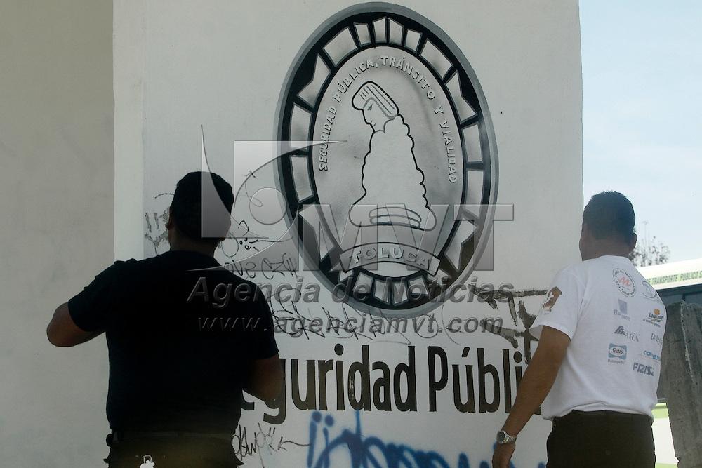 TOLUCA, México.- Dos policías municipales de Toluca quitan las pintas o firmas que fueron colocadas por algunos jóvenes a las afueras del modulo de vigilancia de San Pablo Autopán. Agencia MVT / Crisanta Espinosa. (DIGITAL)