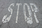 weathered stop signal on an cracked asphalt road