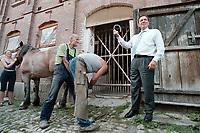 24 AUG 2000, NAUMBURG/GERMANY:<br /> Gerhard Schroeder, SPD, Bundeskanzler, mit einem Hufeisen eines soeben frisch beschlagenen Kaltblutpferdes, auf einem Gehoeft in der Naehe von Naumburg, Sommerreise des Kanzlers durch die Ostdeutschen Bundeslaender<br /> IMAGE: 20000824-01/03-17<br /> KEYWORDS: Gerhard Schröder, Pferd, Tier, horse, animal, Handwerk, Arbeit, work