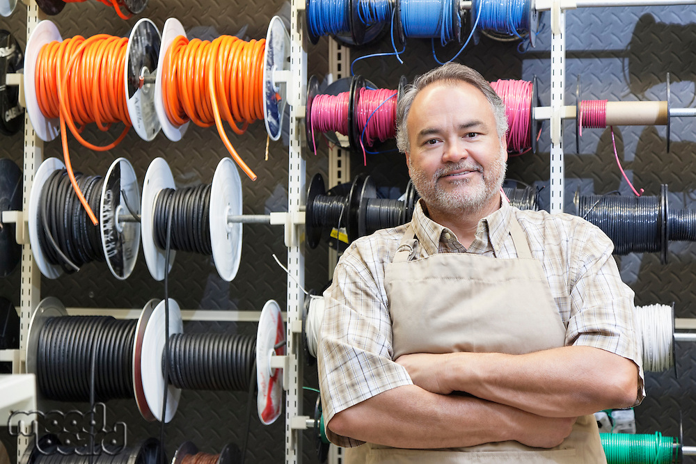 Portrait of a happy mature salesperson standing in front of electrical wire spool with arms crossed in hardware store