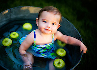 Anabella Dennis, 10 months old, in an old water basin with apples on June 15, 2010. Photography by: Marie Griffin Photography