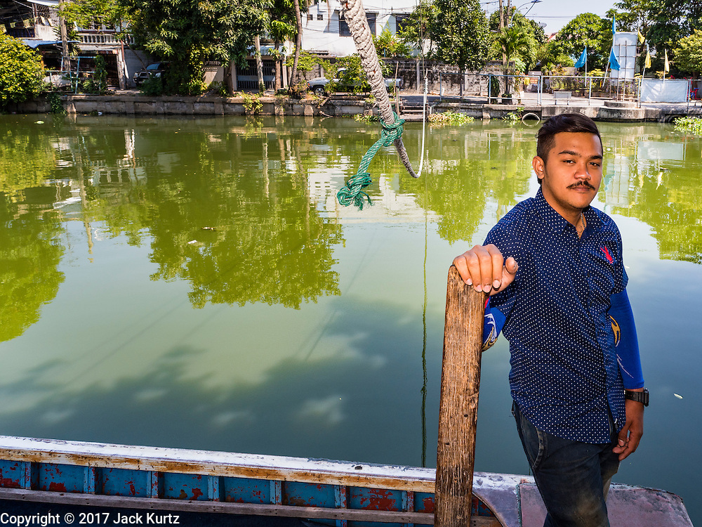 16 FEBRUARY 2017 - THEPHARAK, SAMUT PRAKAN, THAILAND:  A boatman who uses his small boat as a ferry waits for passengers on Khlong Samrung, in the Bangkok suburbs. The boatman pulls it across using a system of ropes and pulleys. He's been working on the boat since he was a child. Small ferries like this used to be common in Bangkok but many of the khlongs (the canals that used to crisscross Bangkok) have been filled in and bridges have been across the remaining khlongs. Now there are only a handful of the ferries left. This ferry charges 2 Baht (the equivalent of about .06¢ US) per person to take a person across the khlong.     PHOTO BY JACK KURTZ
