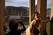 Visitiors of Angkor Wat temple find shelter as a rain storm quickly engulfs the area.