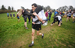 © Licensed to London News Pictures. 08/04/2018. Dorking, UK. Competitors take part in the 2018 annual Wife Carrying Race in Dorking, Surrey. The race, which is run over a course of 380m, with both men and women carry a 'wife' over obstacles, is believed to have originated in the UK over twelve centuries ago when Viking raiders rampaged into the northeast coast of England carrying off any unwilling local women . Photo credit: Ben Cawthra/LNP