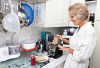 Happy senior woman preparing toast in domestic kitchen