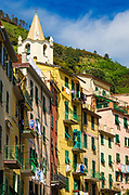 Bell tower and colorful houses in Riomaggiore, Cinque Terre, Liguria, Italy