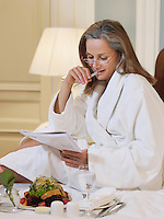 Woman wearing bathrobe sitting on bed reading