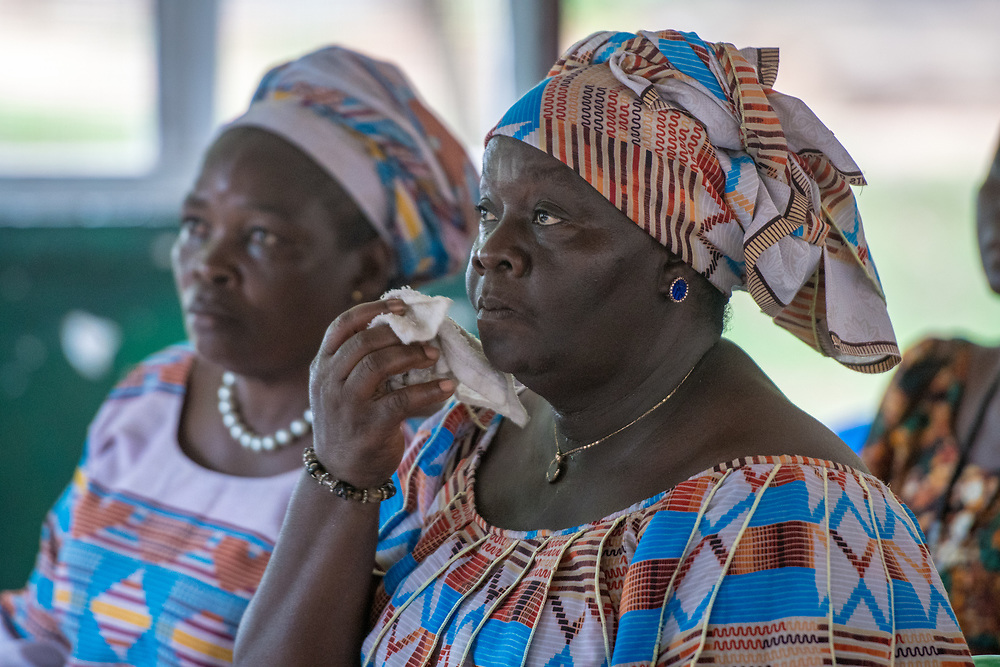A woman listens to a speaker while holding a white facecloth in Ganta, Liberia