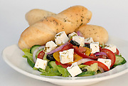 Greek Salad with Feta Cheese containing tomatoes, cucumbers, lettuce, peppers and black olives Seasoned with Zaatar and served with rolls