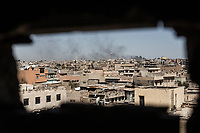 Neighborhoods that ISIS still occupies can be seen through a small hole where Iraqi Federal Police's snipers take up a position in West Mosul, Iraq. Nuri al-Kabir Mosque is seen in the distance. It is the place at which Islamic State&rsquo;s supreme leader Abu Bakr al-Baghdadi gave his famous sermon in 2014 declaring the establishment of the group&rsquo;s rule in Iraq and neighboring Syria.<br /> <br /> イラク警察軍スナイパーの陣地からISISが支配するエリアを覗く。遠くには2014年にISISのリーダー、アブ・バクル・アル・バグダディがいわゆる「イスラム国」の建国とカリフへの即位を宣言したアル・ヌーリモスクが見える。モスル西部、イラク2017年撮影。