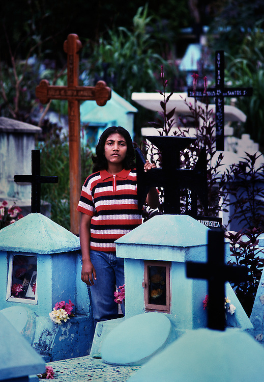 Mina, in the Santa Cruz cemetery. <br /> <br /> She is a survivor of the massacre that took place on this site in 1991, when Indonesian soldiers killed 271 people, who were on a remembrance march for an East Timorese youth who had been killed by the military. <br /> <br /> She was seven years old at the time and was hidden behind the altar of the small church in the cemetery. <br /> <br /> She remembers seeing a New Zealand human rights activist being bayoneted to death at the entrance to the church, by a plain clothed Indonesian.<br /> <br /> East Timor, March 1999.