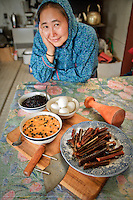 Martha Nicolai with traditional Yup'ik Eskimo foods in her kitchen in Kwethluk, Alaska. She uses an ulu and pestle to prepare berries, eggs, salmon strips, and aqutaq.