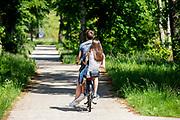 Een jongen rijdt met een meisje achterop over een fietspad tussen Soest en Den Dolder door het bos.<br /> <br /> A boy rides with a girl at back of his bike on a cycle path between Soest and Den Dolder in the woods.