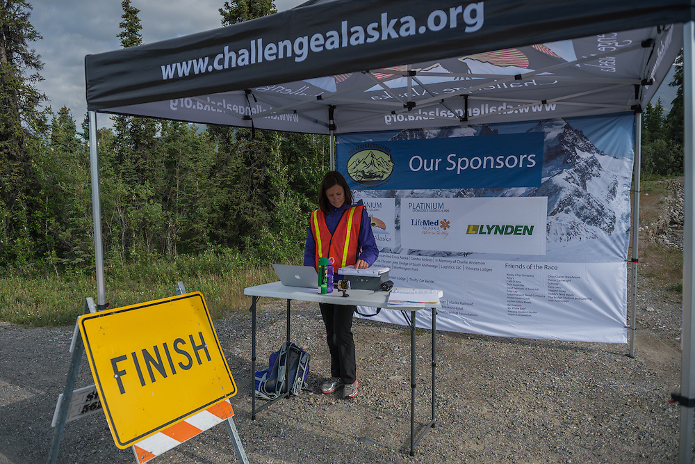 July 25, 2015: Official timer Kate Wondra tabulates the final finishing times after stage five of the 2015 Alaska Challenge handcycle race.