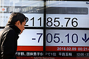 A pedestrian walks past an electronic stock board of a securities firm in Tokyo, Friday, Feb. 9, 2018. Asian shares have opened lower and are tracking the overnight plunge on Wall Street. The Dow Jones industrial average plunged more than 1,000 points as a weeklong market swoon continued.09/02/2018-Tokyo, JAPAN