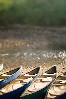 Canoes in a row along the rocky river bank waiting for canoeist to take them out into the white water