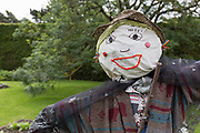 The face of an embroidered scarecrow in a garden at the Royal Botanical Gardens in Edinburgh, on 26th June 2019, in Edinburgh, Scotland. The Royal Botanic Garden Edinburgh (RBGE) is a scientific centre for the study of plants, their diversity and conservation, it was founded in 1670 as a physic garden to grow medicinal plants.