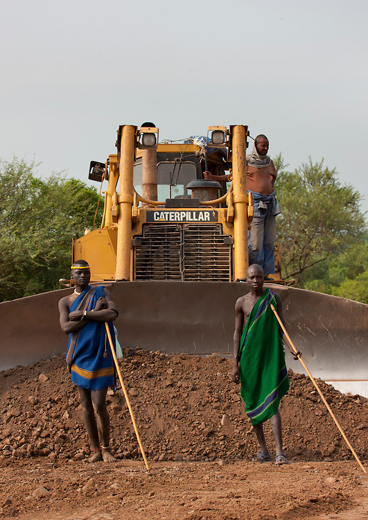Two indigenous Mursi men standing in front of a caterpillar steam shovel on coated road.  Construction work in Mago Park, Omo Valley, Ethiopia.<br /> <br /> In south Ethiopia, the Omo river and its fertile lands, home of famous tribes like Mursi or Nyangatom, now cut off by the Gib&eacute; III dam, are siphoned off to irrigate the new giant farms run by foreign companies from Malaisia, India, Saudi Arabia... The Ethiopian government having taken land from some tribes has forced them to move and often wind up in enemy territory: Dizi/Surmas, Nyangatom/Karo, Bodis/Mursi, Karrayyu/Afars. At Mago Park, a UNESCO site, on Mursis territory and in the region of Hana, home to the Bodis, the bulldozers are hard at work. The 200000 inhabitants of the southern tribes are considered &laquo;behind the times &raquo; by Addis. Fear has gripped the area due to ferocious repression: prison, torture, beatings... Today, the tribes around Omo are self-reliant thanks to crops, cattle, a few tourists and some exchanges. A fragile stability.