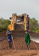 Two indigenous Mursi men standing in front of a caterpillar steam shovel on coated road.  Construction work in Mago Park, Omo Valley, Ethiopia.<br />