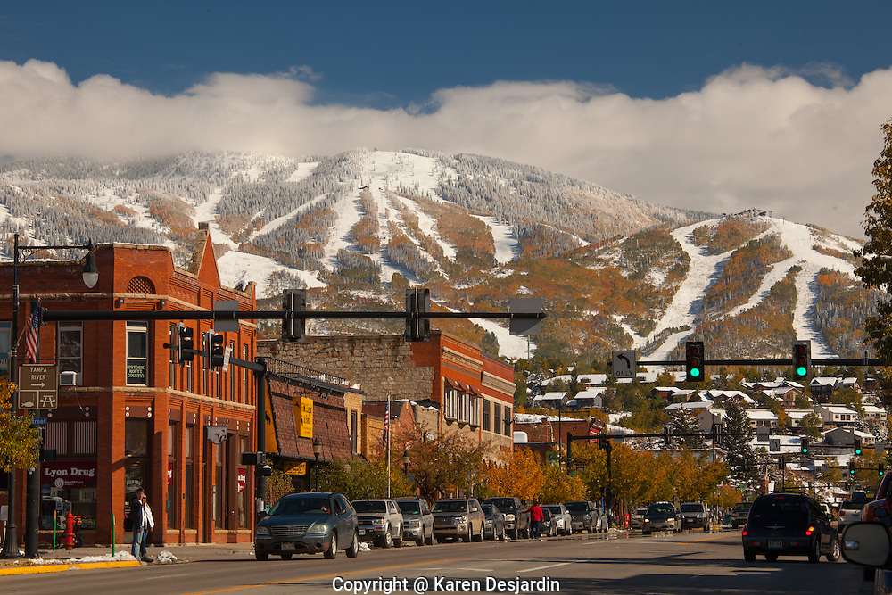 The Steamboat Springs ski resort, with fall colors and early snow, forms a backdrop to the downtown of Steamboat Springs, Colorado.